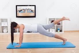 woman practicing yoga at home standing on a mat on her living