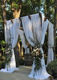 picture of wedding pergola with white curtains and lush florals