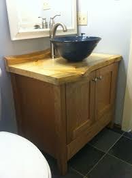 bahtroom dark bowl sink on pine bathroom vanity and soft wall