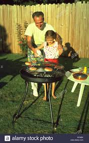 a man helps a little cook hamburgers outside on a charcoal