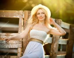 beautiful blonde with country look near an old wooden fence