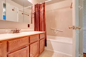 light pink bathroom with wooden washbasin cabinet tile floor