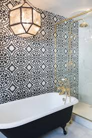 black claw foot tub next to glass and brass shower enclosure