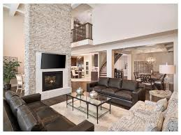 carpeted stairs leather sofa tall ceilings built in fireplace