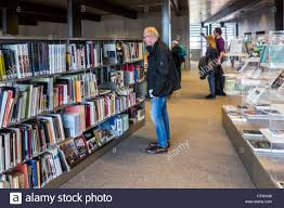 Read Bookshelves by Elderly Man Choosing Book To Read From Rows Of Books In