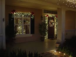 lighted garland around door and wreath merry y all