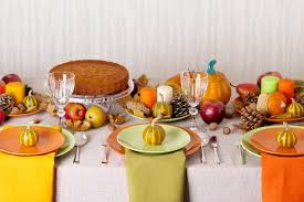thanksgiving dinner seasonal table setting with autumn leaves