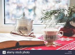 winter still life open book glasses teapot cup of tea and