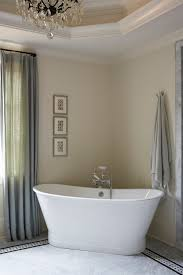 white stand alone bath tub placed in corner of bathroom amy