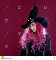 background halloween images scary witch with red hair performs magic on a pink background