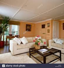 eighties sittingroom with peach colored walls and cream sofa and