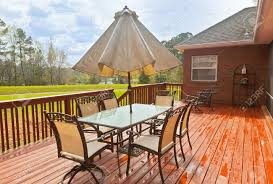 large wooden backyard deck with patio furniture and a view of