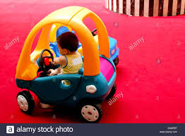 kid car small kid driving toy car inside a play house at a shopping mall