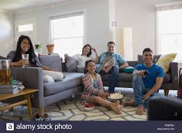 Family Watching TV With Popcorn In Living Room Stock Photo - Family in living room