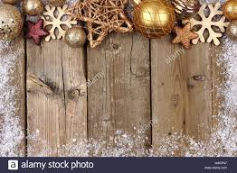 gold ornament top border with snow frame on a rustic wood