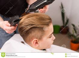little boy getting haircut by barber stock photo image 87654781