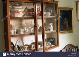 old glass doors close up of antique china on shelves in old wall cupboard with