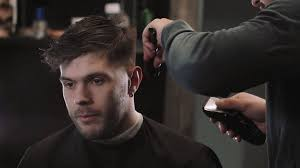 handsome man doing a haircut for man with black hair at barber