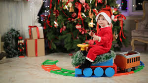 little in santa costume goes on toy plastic train near