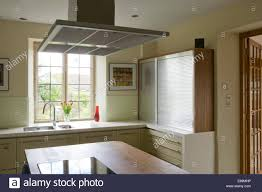extractor fan above central island unit in modern kitchen stock