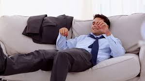 Tired Businessman Lying On A Sofa In The Waiting Room Stock - Lying sofa 2