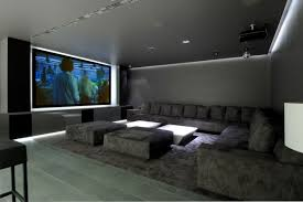 basement home theater with grey walls and sectional sofa