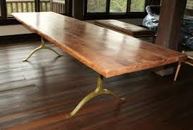 varnished long solid wood dining table with iron legs above wood