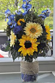 nicole ryan s centerpiece made from a mason jar filled with blue and yellow flowers sunflowers gerbera daisies deep blue pom poms and light blue delphiniums