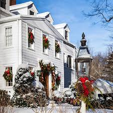a white new england farmhouse complete with holly bushes out