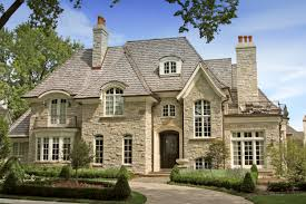 white brick french house with dark roof tile and black wooden