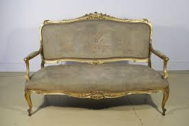 a louis xv canapé with arched padded back and bowed seat covered in
