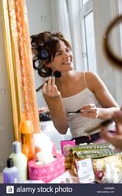 young woman using makeup brush in front of mirror with hair in