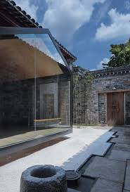 a glazed meditation room overlooks traditional courtyard in