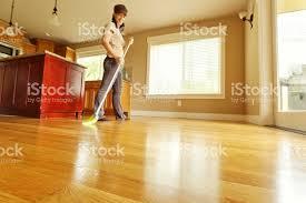 sweeping hardwood floor with broom stock photo 185235158