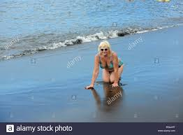 Volcanic Sand On All Fours Portrait Of Aged Woman On Background Of Surf On Wet