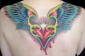 a color tattoo of a flying bleeding heart the wings look a bit