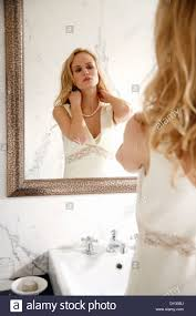 woman looking at herself in the bathroom mirror stock photo