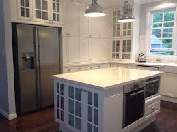 white solid wood counter island with light gray marble top and