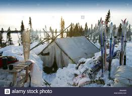 a wall tent in the snow at a remote arctic winter camp near old