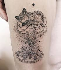 hands cradling baby fox over mystical campfire best tattoo