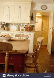 pine table and chairs in cream country kitchen with terracotta