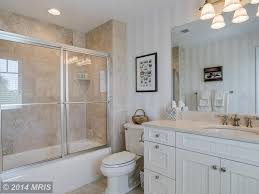 traditional full bathroom with limestone u0026 flat panel cabinets in