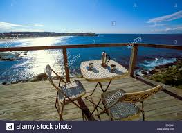 Chairs On A Beach Coffee Cups And Pot On A Table With Two Chairs On A Balcony Stock