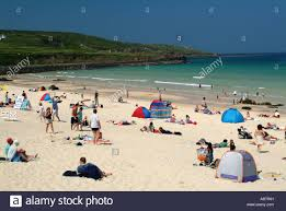 St Ives Beach House People Sunbathing On Beach At St Ives Cornwall Stock Photo