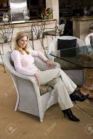 portrait of smiling mature woman sitting in white wicker chair
