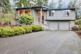 simple grey brown split level with two garage doors stock photo