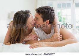 Kiss In Bed Relaxed Couple Kissing In Bed Stock Photo Royalty Free Image
