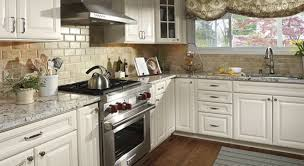 french country kitchen with white cabinets recessed lighting and drum pendant lighting what color backsplash