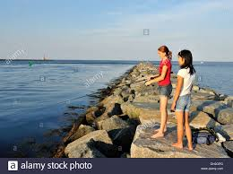two teenage girls fishing off the east jetty of the cape cod canal