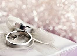 silver boxes with bows on top pair of wedding rings on top of silver gift box with bow bokeh